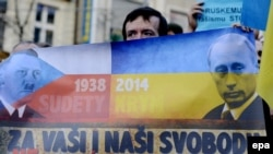 Czech Republic – Protestor holds anti Putin banner during a rally in protest against the Russian military actions in Crimea, in Prague, Czech Republic, 08 March 2014