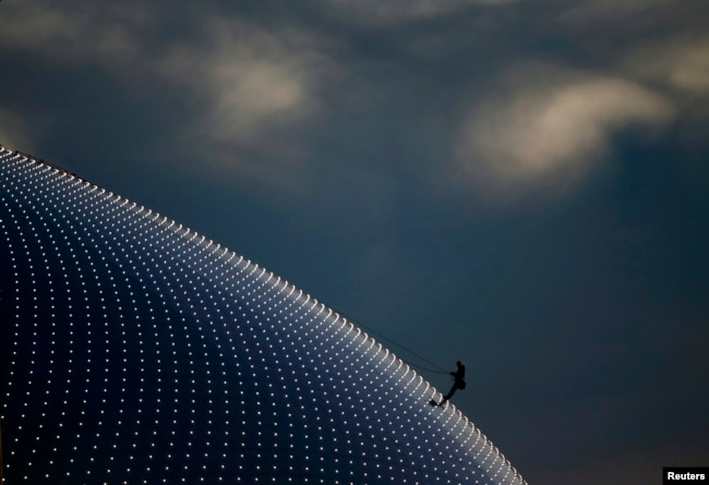 Russia -- A person climbs on the Bolshoi Dome, one of the ice hockey venues, before the medals ceremony during the 2014 Sochi Winter Olympics, February 14, 2014