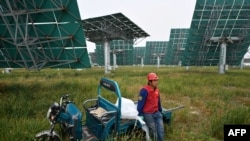 CHINA – A worker waits to replace mirrors on heliostats used for reflecting sunlight at the Yanqing Solar Thermal Power Generation Base in Yanqing, north of Beijing, on Sept. 28, 2020.