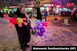 RUSSIA -- An elderly woman sells colored balloons to earn extra money for her retirement standing near a big shopping mall in Moscow, January 25, 2016