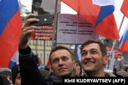 RUSSIA -- Russian opposition leader Alexei Navalny and his brother Oleg take a selfie picture during a march in memory of murdered Kremlin critic Boris Nemtsov in central Moscow on February 24, 2019.