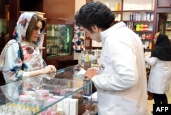 """An Iranian woman shops at a drugstore at the Nikan hospital in Tehran on September 11, 2018. - Judges at the International Court of Justice in The Hague unanimously ruled Washington should remove barriers to """"the free exportation to Iran of medicines."""""""