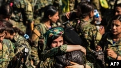 Female fighters of the Syrian Democratic Forces (SDF) gather during a celebration at the iconic Al-Naim square in Raqa on October 19, 2017, after retaking the city from Islamic State (IS) group fighters. The SDF fighters flushed jihadist holdouts from Raqqa.