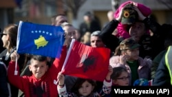 KOSOVO -- Kosovars waving national flags pose for a photo, during celebrations to mark the 11th anniversary of independence, in Pristina, February 17, 2019