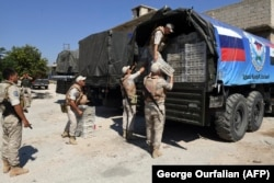 SYRIA -- Russian soldiers unpack aid, from Russia and the Chechen Ahmed Kadyrov fund, in the northern Syrian town of Tal Rifaat, August 8, 2018