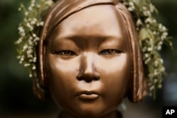 """A statue commemorating so-called """"comfort women,"""" a euphemism given by Japan to the women and girls enslaved for sex by the Japanese army during World War II, in a residential area in central Berlin, Germany on October 9, 2020. Markus Schreiber/AP"""