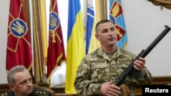 Ukraine -- An Ukrainian military commander (R) shows a rifle seized from Russian soldiers as General Staff commander Viktor Muzhenko looks on during a news conference in Kyiv, May 18, 2015
