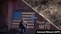 KOSOVO -- A man walks past graffiti reading 'Thank You NATO' and featuring the U.S. flag near the village of Stagovo, March 24, 2019