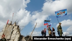 UKRAINE -- Local people hold flags of the self-proclaimed Donetsk Peoples Republic (DPR) and Russia as they stand on the damaged Savur-Mohyla memorial not far from the pro-Russian rebel's controlled Donetsk city, Ukraine, September 7, 2017