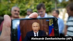 RUSSIA -- A man watches on his smartphone Russian President Vladimir Putin's televised address on pension reform, in Moscow, August 29, 2018