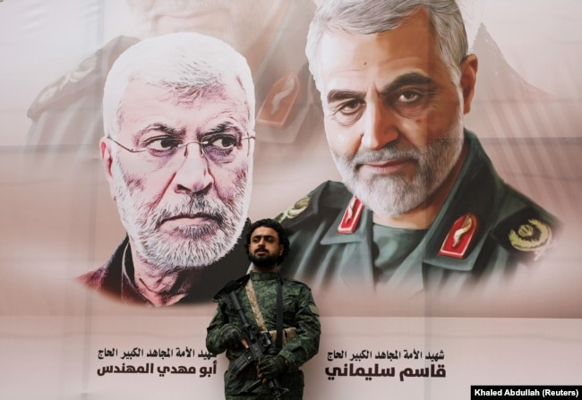 YEMEN -- A Houthi militant stands by a billboard with posters of Iraqi militia commander Abu Mahdi al-Muhandis and Iranian military commander Qassem Soleimani during a rally by Houthi supporters to denounce the U.S. killing of both commanders.