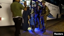 ISRAEL - People walk past Israeli soldiers as they board a bus during the Syria Civil Defence, also known as the White Helmets, extraction from the Golan Heights, Israel in this still image taken from video, provided by the Israeli Army July 22, 2018.