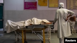 A man stands next to the body of his wife, who died due to breathing difficulties, inside an emergency ward of a government hospital in Bijnor, Uttar Pradesh, India, May 11, 2021.