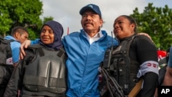 Nicaraguan police take a photo with President Daniel Ortega (center) after weeks of unrest in Masaya, Nicaragua, on July 13, 2018. (AP Foto/Cristobal Venegas)
