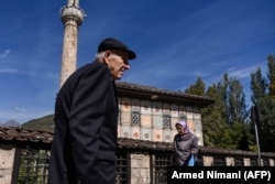 "MACEDONIA -- Albanians walk past a mosque in the town of Tetovo, near Skopje, on September 28, 2018, ahead of a referendum on whether to change the country's name to ""Republic of Northern Macedonia""."