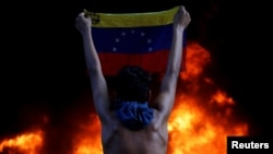 CARACAS – A protester holds a national flag as a bank branch, housed in the magistracy of the Supreme Court of Justice, burns during a rally against Venezuela's President Nicolas Maduro, in Caracas, Venezuela, June 12, 2017.