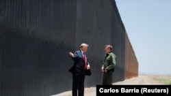 U.S. President Donald Trump talks with U.S. Border Patrol Chief Rodney Scott as he tours a section of the U.S.-Mexico border wall.