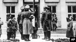 German and Russian officers salute the Nazi swastika flag during a parade in Brest-Litovsk celebrating a border demarcation in Poland on September 22, 1939, following Hitler's invasion of Poland (September 1, 1939). Brest-Litovsk, September 22, 1939