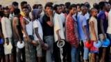 Ethiopian men who fled war in the Tigray region queue for food at the Um-Rakoba camp, on the Sudan-Ethiopia, November 19, 2020.