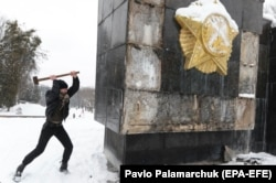 UKRAINE -- A man uses a sledgehammer to damage the Glory Monument in the western of Lviv, February 15, 2018