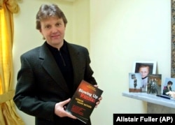 "U.K. – Aleksandr Litvinenko, former KGB poses with his book ""Blowing Up Russia: Terror From Within"" at his home in London in this Friday, May 10, 2002"