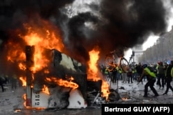 FRANCE -- A man throws a bike in a burning truck during a protest of Yellow vests (Gilets jaunes) against rising oil prices and living costs near the Arc of Triomphe on the Champs Elysees in Paris, on November 24, 2018.