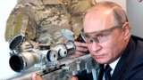 RUSSIA -- Russian President Vladimir Putin aims a sniper rifle during a visit to the Patriot military exhibition center outside Moscow, September 19, 2018