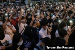 Pro-democracy demonstrators in June 2020 shine flashlights on their mobile phones to mark the one-year anniversary of a mass rally against a controversial extradition bill.