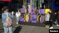 """People take a selfie in front of a """"Move on 2020!"""" sign in Times Square amid the coronavirus disease (COVID-19) pandemic in the Manhattan borough of New York City, New York, U.S., December 28, 2020. REUTERS/Carlo Allegri"""