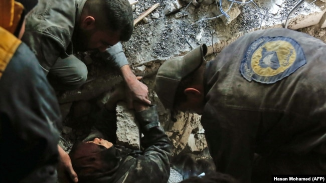 SYRIA -- Volunteers of the Syrian Civil Defense, known as the White Helmets, rescue a woman from the rubble of a building after an air strike in Douma, Eastern Ghouta, March 19, 2018