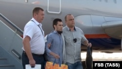 RUSSIA -- A Tatarstan-born Russian national (born in 1988, center), who has been extradited by Greece to Russia, is escorted at an airport in the Moscow region, August 30, 2018