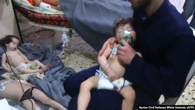 SYRIA -- Unidentified volunteers give aid to children at a hospital following an alleged chemical attack on the rebel-held town, April 8, 2018