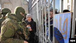 Ukraine -- A Ukrainian woman speaks with armed men in military uniform, believed to be Russian Soldiers, who block Ukrainian navy base in Novoozerniy village near of Yevpatoriya, Crimea, March 3, 2014