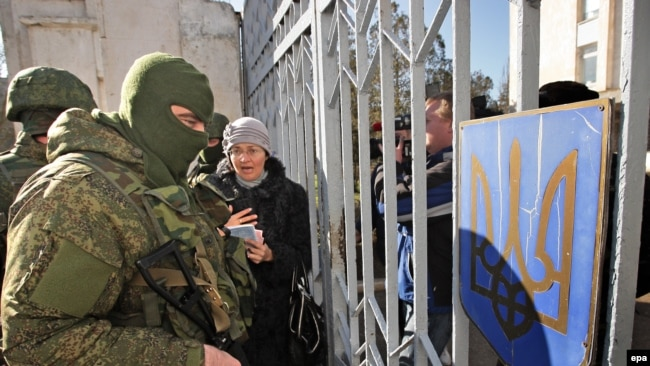 Ukraine -- A Ukrainian woman speaks with armed men in military uniform, believed to be Russian Soldiers, who block Ukrainian navy base in Novoozerniy village near of Yevpatoriya, Crimea, March 3, 2014