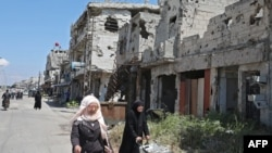 Syrians walk past buildings heavily damaged during Syria's civil war, in the central city of Homs, on April 28, 2020.
