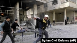 SYRIA -- Members of the Syrian Civil Defense group carry a man who was wounded during airstrikes and shelling by Syrian government forces, in Ghouta, a suburb of Damascus, February 20, 2018