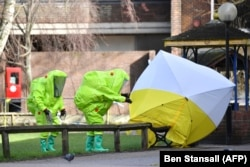Emergency services in green biohazard suits affix a tent over the bench where poisoning victims were found on March 4 in critical condition at The Maltings shopping centre in Salisbury, southern England, on March 8, 2018.