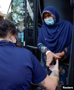 A woman takes the hand of a security officer as she and other people arrive at a processing center for refugees evacuated from Afghanistan at the Dulles Expo Center in Chantilly, Virginia, August 23, 2021.