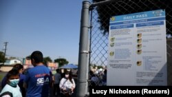 People wait in line at a school for coronavirus disease (COVID-19) testing and vaccines in South Gate, Los Angeles, California, U.S., August 12, 2021.