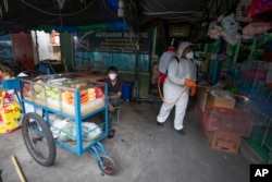 A worker sprays disinfectant as a precaution against the new coronavirus near a fruit vendor at Chatuchak Market in Bangkok, Thailand, on March 20, 2020.