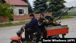 Moldova -- People ride a tricycle motorbike in Dobrogea village next to Balti, Moldova on October 10, 2013.