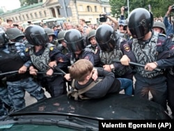 RUSSIA -- Russian police officers push a teenager during a rally protesting retirement age hikes in St. Petersburg, September 9, 2018