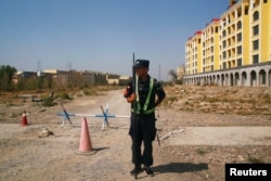 A Chinese police officer takes his position by the road near what is officially called a vocational education center in Yining, Xinjiang Uyghur Autonomous Region, China on September 4, 2018.
