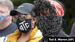 Protesters wear masks to help prevent the spread of the coronavirus, June 5, 2020, in Tacoma, Wash.