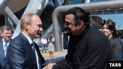 Russia -- Russian President Vladimir Putin (L) talks to U.S. actor Steven Seagal (R), while visiting the oceanarium on Russkiy island outside Vladivostok, Primorsky Krai, September 4, 2015