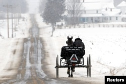 An Amish wagon makes its way north on County Road 1353 during a light snowfall near Ashland, Ohio, U.S. February 1, 2021. Tom E. Puskar/Times-Gazette.com/USA TODAY NETWORK via REUTERS.