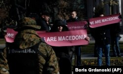 "MACEDONIA -- A group of people hold banners reading ""We are Macedonia"" during anti NATO protest in front of the Parliament in Skopje, Macedonia, while NATO Secretary General Jens Stoltenberg addresses the lawmakers in the Parliament building, Thursday, Ja"