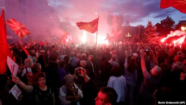 """MACEDONIA -- Opponents of the deal between Greece and Macedonia on the latter country's new name """"North Macedonia"""" light flares while protesting outside the parliament in Skopje, Macedonia, Saturday, June 23, 2018."""