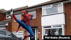 Jason Baird is seen dressed as Spiderman during his daily exercise to cheer up local children in Stockport, Britain, April 1, 2020