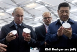 RUSSIA -- Chinese President Xi Jinping, right, and Russian President Vladimir Putin look at containers of food as they visit an exhibition during the Eastern Economic Forum in Vladivostok, Russia, Tuesday, Sept. 11, 2018